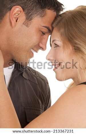 A man and woman with their heads together with smiles, looking into each others eyes. - stock photo