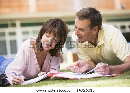 A man and woman writing notes while lying on a campus lawn - stock photo