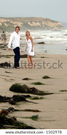A man and women strolling down the beach laughing and having fun
