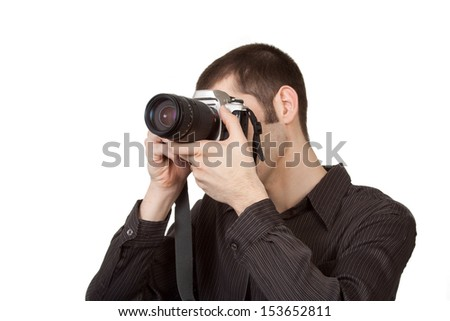 A man angled away from the camera prepares to take a photograph. Lots of room for copy.  - stock photo