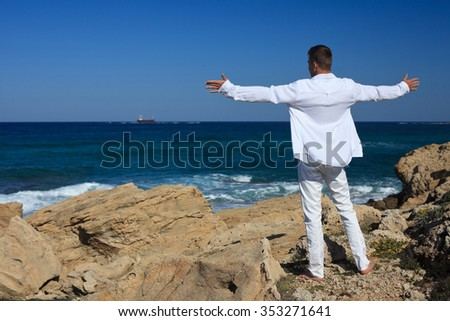 A man arms spread looking at sea  - stock photo