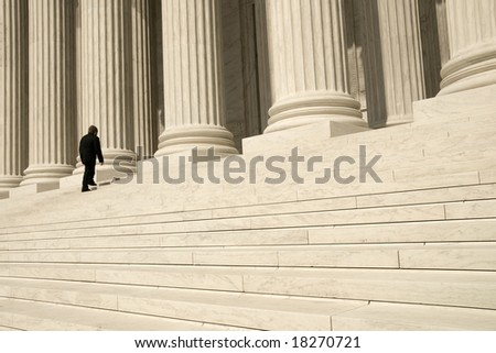 A man ascending the steps at the entrance to the US Supreme Court in Washington, DC. - stock photo