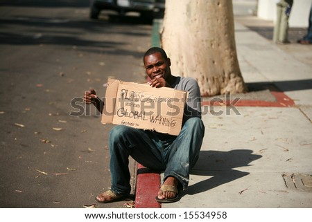 a man asks for donations to help stop Global Warming with his cardboard sign - stock photo