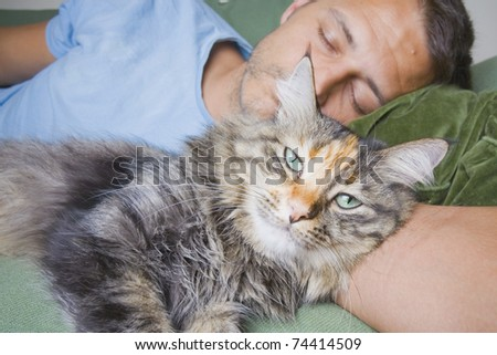 A man asleep on his sofa with a cute cat