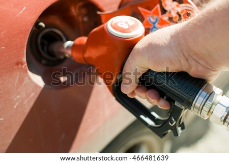 a man at a gas station fills the fuel in the vehicle tank