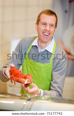 A man at a grocery store selling a lobster - stock photo