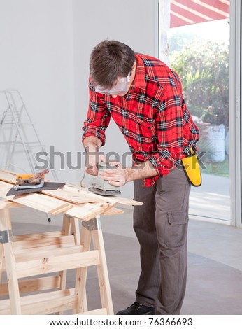 A man at home using an electric hand sander with safety goggles - stock photo
