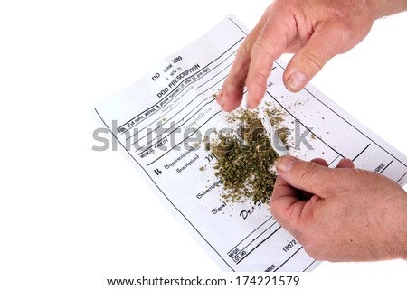 "A man attempts to roll a ""Joint"" out of Marijuana on his new Prescription for Legal Pot to help cure his Hiccups or some other such nonsense.  Many States are considering legalizing pot as medicine.  - stock photo"