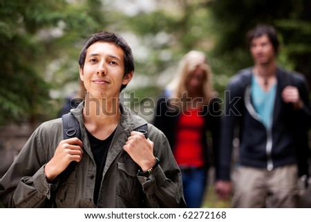 A man backpack camping in the forest with a group of friends in the background - stock photo