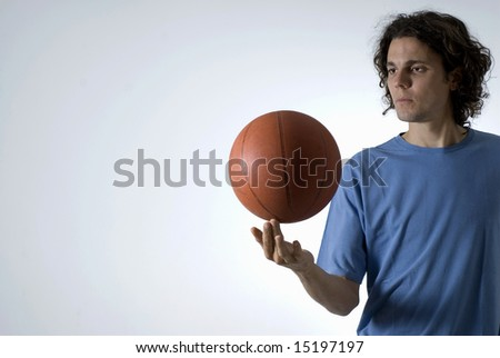 A man balancing a basketball with two fingers.  He is staring at the basketball. Horizontally framed shot. - stock photo