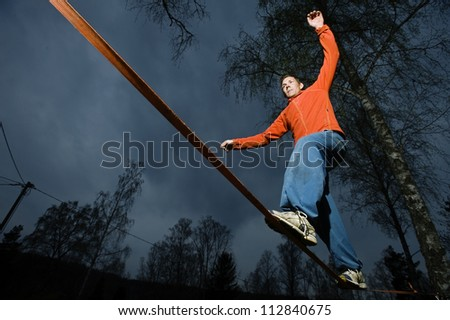 A man balancing on a cord. - stock photo