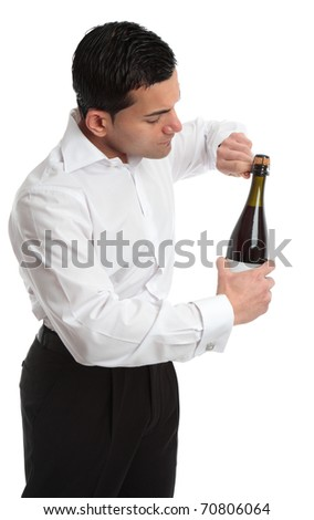 A man, bartender or waiter opens a bottle of champagne, sparkling wine.  He is untwisting the metal cage around the cork.  Sideview.   White background. - stock photo