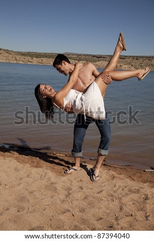 A man bending his girl in his arms she has a surprised expression on her face. - stock photo