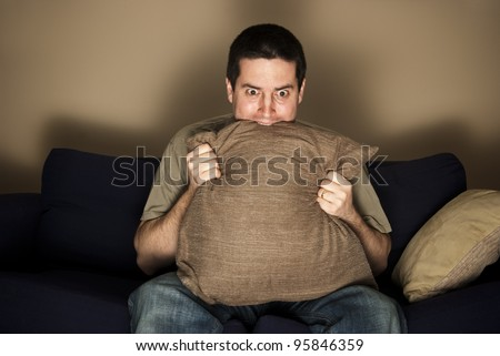A man bites a pillow in fear and nervousness while watching TV - stock photo