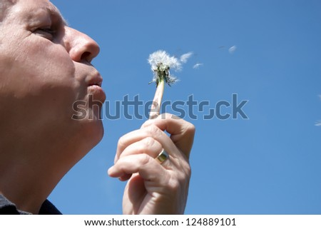 A man blowing seeds off a dandelion - stock photo