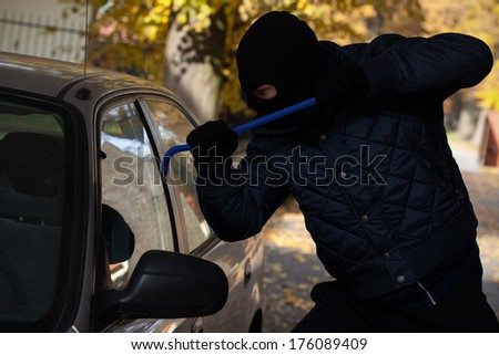 A man breaking in a car through its window - stock photo