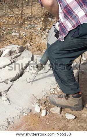 A man breaking up concrete with a jack hammer - stock photo