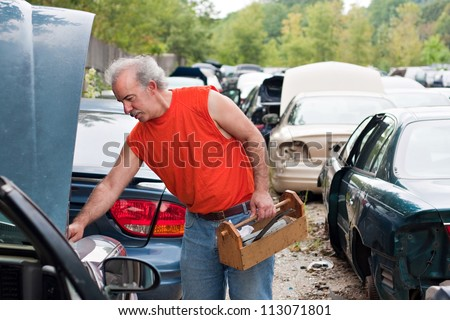 A man browses for car parts on decommissioned used cars at an automotive junk yard. - stock photo