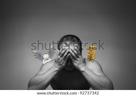 A man burying his face in his hand in a despair mood while his conscience is torn between the temptation of an evil golden devil and promises of a holy baby angel. - stock photo
