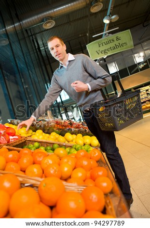 A man buying fresh fruits and vegetables at a grocery store - stock photo