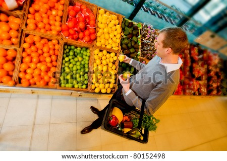 A man buying fruit in a grocery store - stock photo