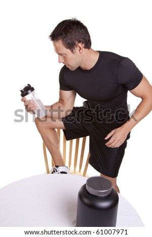 A man by a table with a protein drink - stock photo