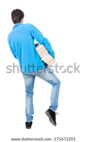 A man carries a heavy pile of books. back view. Rear view people collection.  backside view of person.  Isolated over white background. Student operas on foot stack of heavy books. - stock photo