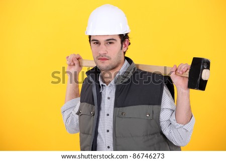 A man carrying a sledgehammer. - stock photo