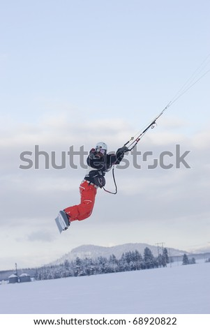A man catches air on a snow kite in northern Idaho. - stock photo