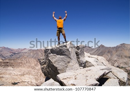 a man celebrates his success on the summit of Mount Cotter