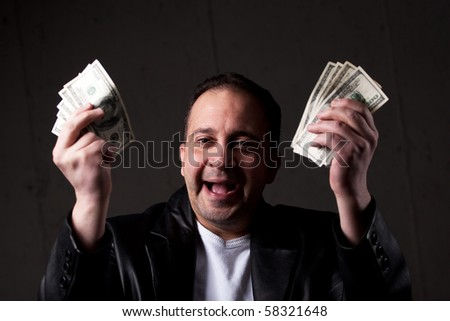 A man celebrating holding handfuls of green American cash money. Shallow depth of field with focus on the face. - stock photo