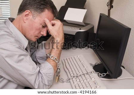 A man chained to his computer with an expression of fatigue or intense boredom. - stock photo