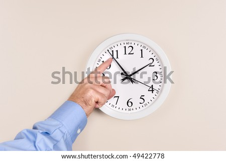 A man changes the time on a clock, moving it forward in time, spring forward. - stock photo