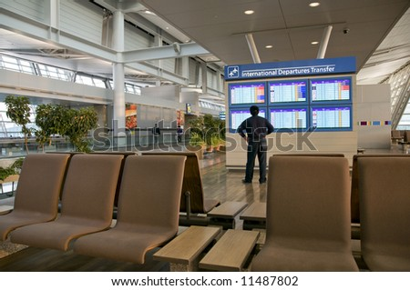 a man checking arrivals and departure schedule at international airport