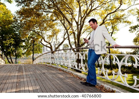 A man checking his cell phone in a park
