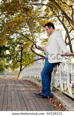 A man checking his cell phone in a park - stock photo