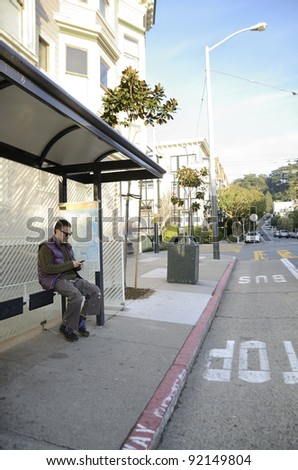 A man checking his cellphone while waiting at a bus stop - stock photo