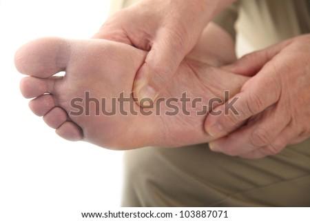 a man checks his aching foot - stock photo