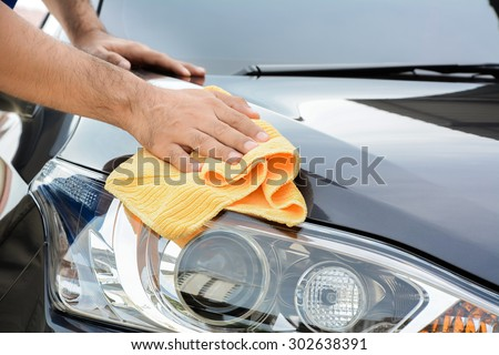 A man cleaning car with microfiber cloth, car detailing (or valeting) concept - stock photo