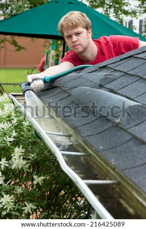 A Man Cleaning Gutters With A Water Hose - stock photo