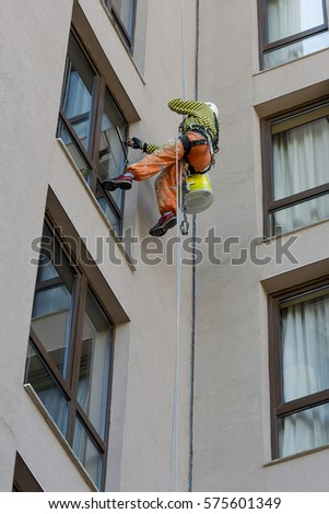 A man cleaning mirror window on a high rise building.Climber on job as Professional windows cleaner