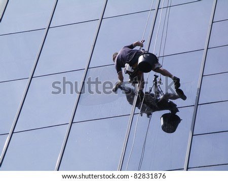 A man cleaning windows on a high rise building