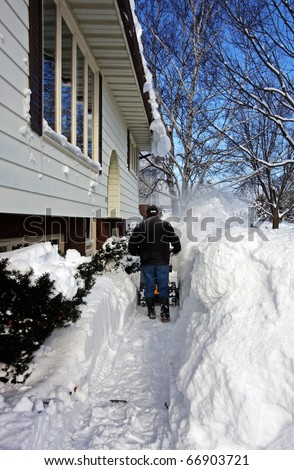 a man clearing snow with a snowblower - stock photo