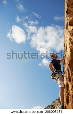 A man climbing up a really steep mountain attached to a harness and rope looking up against a blue sky in the outdoors