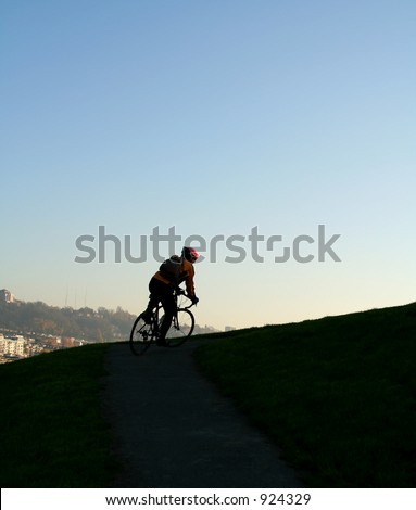 A man climbing uphill on a bicycle showing effort and determination - stock photo