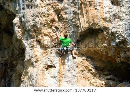 A man climbs a wall. - stock photo