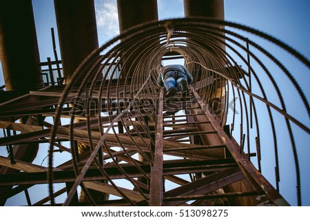 a man climbs up an old rusty vertical ladder factory