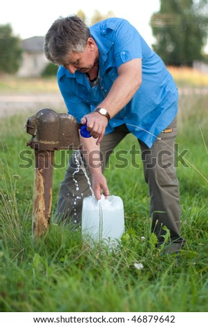 A man collects the water from the old fashioned water pump