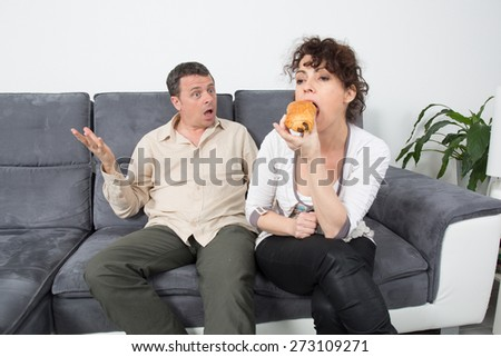 A Man complains about what's eating his wife on sofa