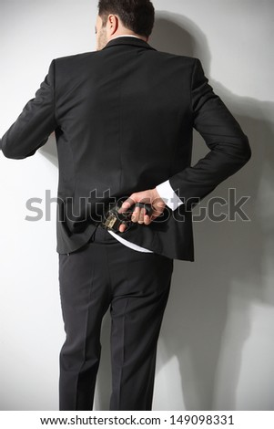 A man conceals a firearm in the back of his pants - stock photo